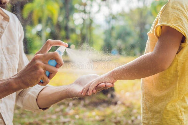 Sprej för farsa- och sonbruksmygga Bespruta krypimpregneringsmedlet på utomhus- hud fotografering för bildbyråer