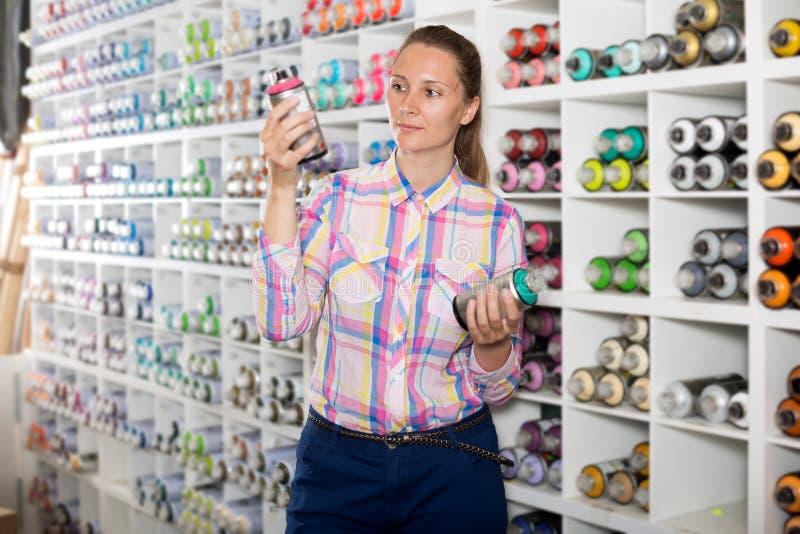 Sprej för kvinnakundinnehav med färgmålarfärg arkivfoton