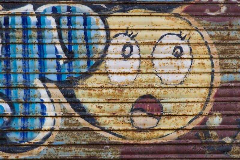 Sprej målade grafitti på metallrullgardinen arkivfoton