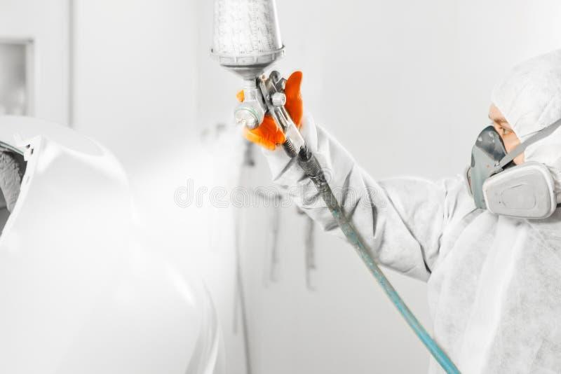 Sprejmålarearbetare i skyddande handske med kroppen för bil för retuschsprutapulverizermålning i den vita målarfärgkammaren arkivbild