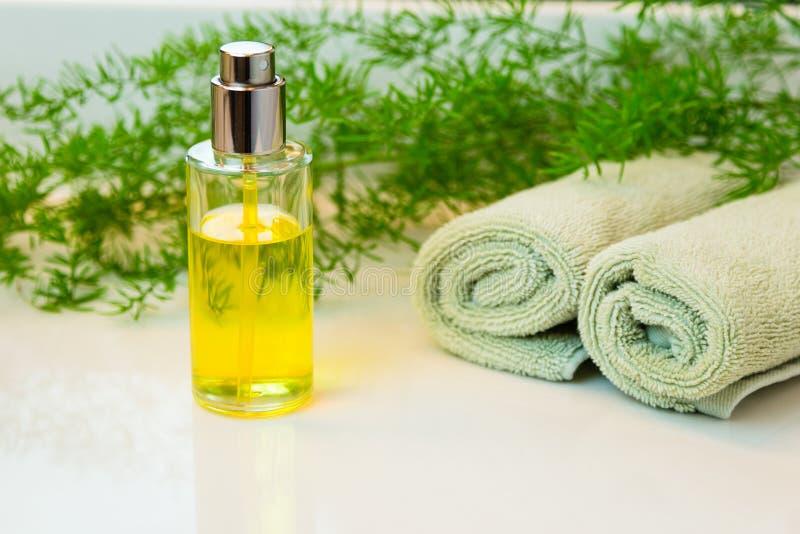 Sprejmistflaska, handdukar och gräsplaner på badrumcountertop royaltyfri fotografi