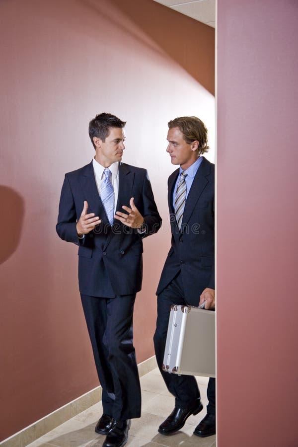 Spreken van zakenlieden, die in bureaugang loopt royalty-vrije stock afbeelding