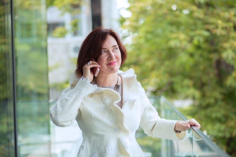 Sprekend bij telefoon, rijpe vrouw die cel gebruiken royalty-vrije stock fotografie