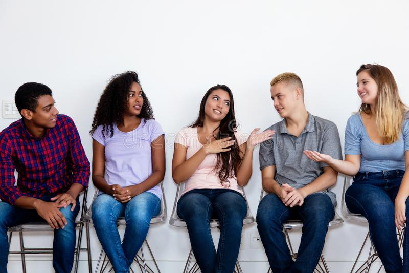 Sprekende jonge volwassen groep mensen in wachtkamer royalty-vrije stock foto's