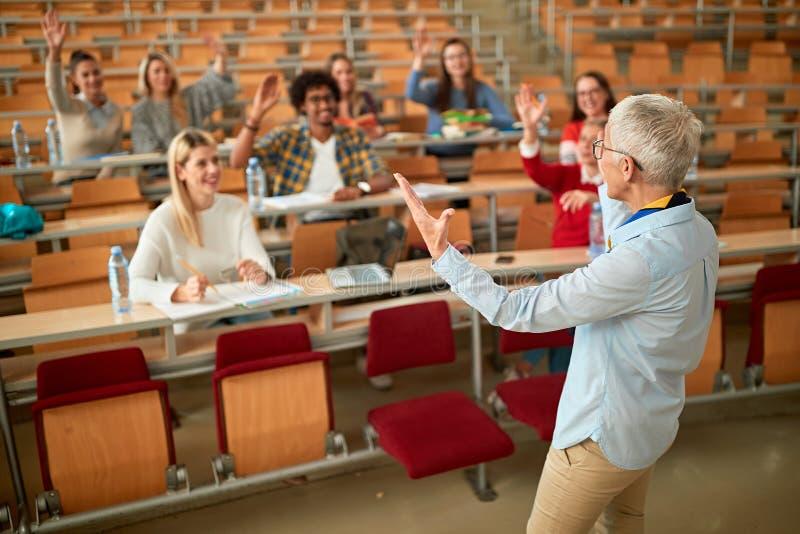 Spreker op universiteit - studenten die aan leraar in het klaslokaal op universiteit luisteren royalty-vrije stock fotografie
