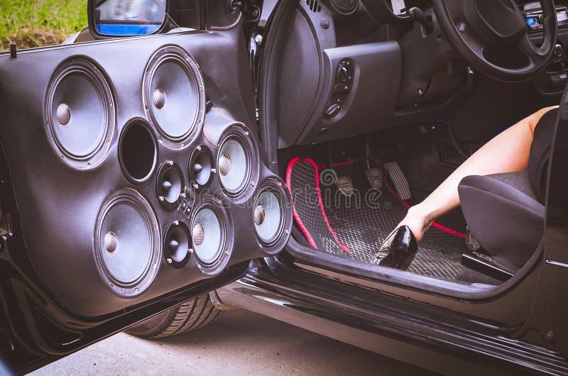 Sprekers van het auto de Audiosysteem in de Geopende Deur met een Vrouw in Hoge Hielen gedeeltelijk Zichtbare Zitting in de Bestu royalty-vrije stock fotografie