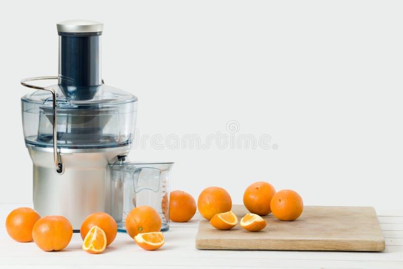 Spremiagrumi elettrici moderni ed arance fresche, fondo bianco immagine stock