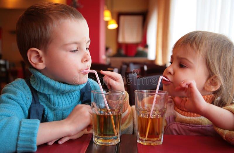 Spremuta della bevanda della ragazza e del ragazzino fotografie stock
