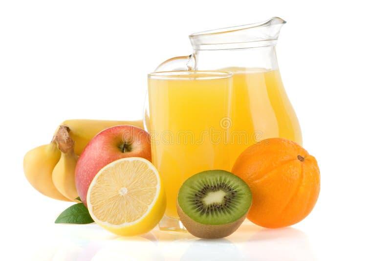 Spremuta della frutta fresca in vetro e fette su bianco fotografia stock