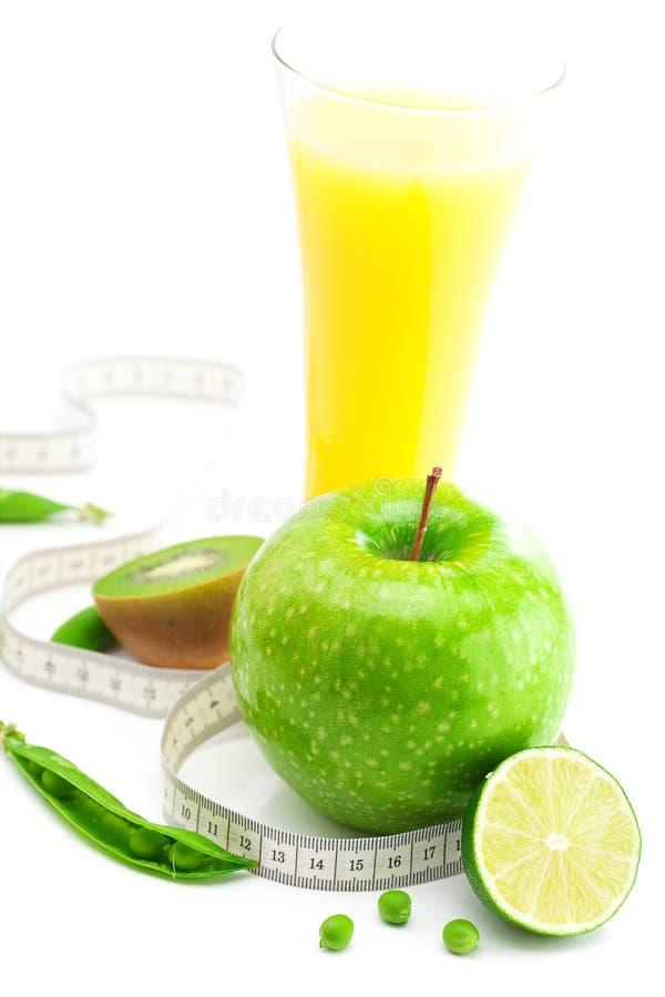 Spremuta, mela, calce, piselli, kiwi e nastro di misura fotografia stock libera da diritti