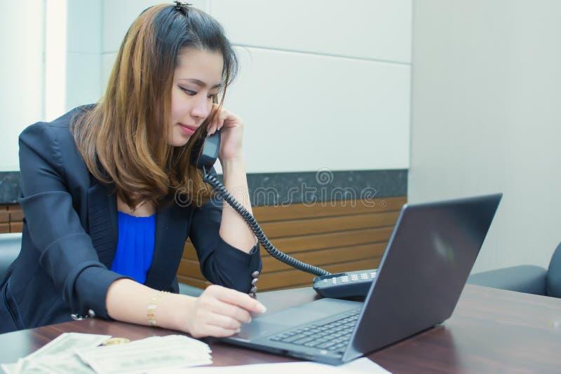 spricht asiatische 30s Geschäftsfrau am Telefon beim Arbeiten stockfoto