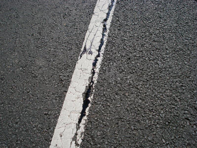 Spricka för vit linje och asfalt royaltyfri foto