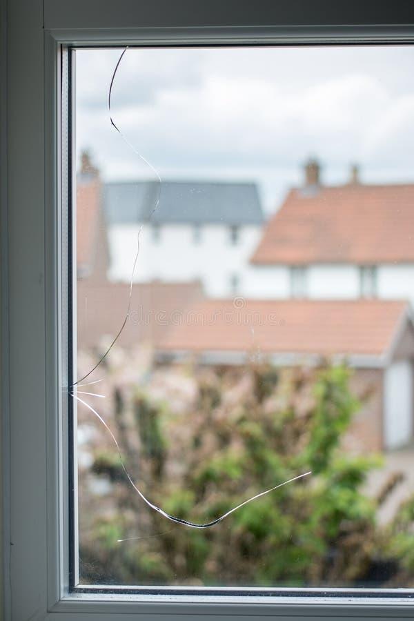 Sprickan i det glass fönstret förser med rutor fotografering för bildbyråer