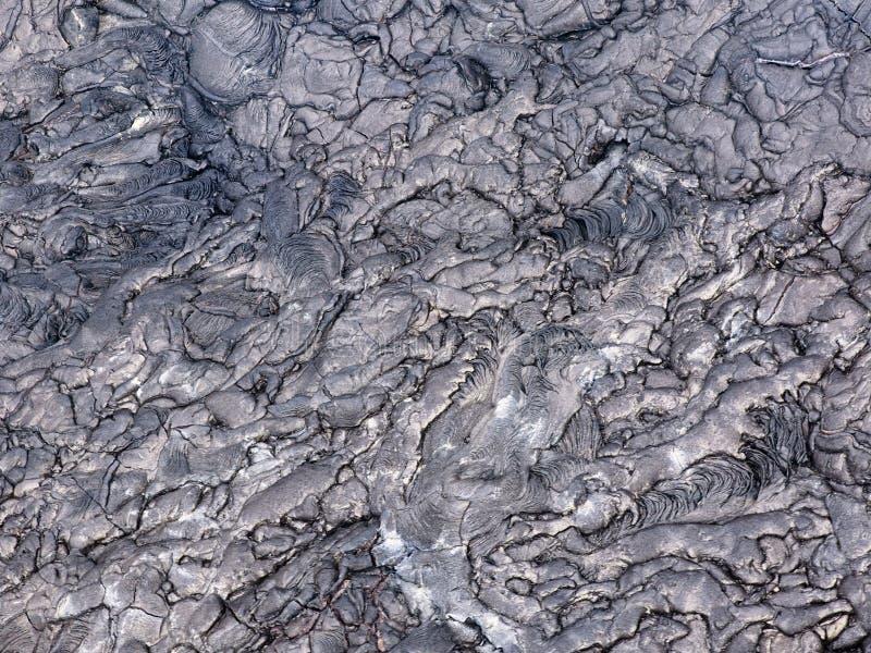 Sprickor och former dyker upp från denna övre del för slutet av svart överförd till fast form lava på ön av Hawaii royaltyfria foton