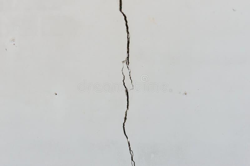 Sprickor på den fast vit målade betongväggen arkivfoton