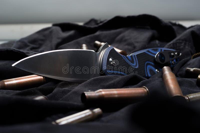 Spridda ammunitionar på en svart bakgrund Kassetter och kniv arkivbilder