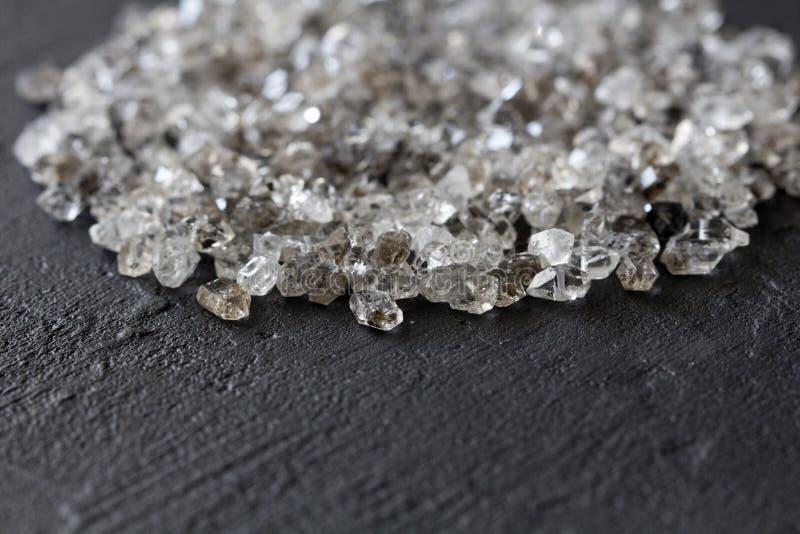 Spridda diamanter p? en svart bakgrund R? diamanter och bryta, en spridning av naturliga diamantstenar Grafitkvarts arkivfoton