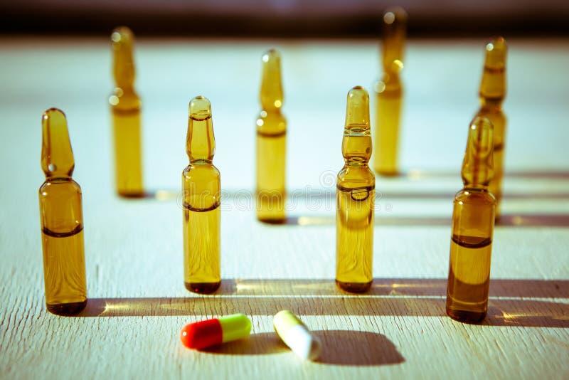 Spridda minnestavlor, preventivpillerar, ampuller för injektion på träbackg arkivbilder
