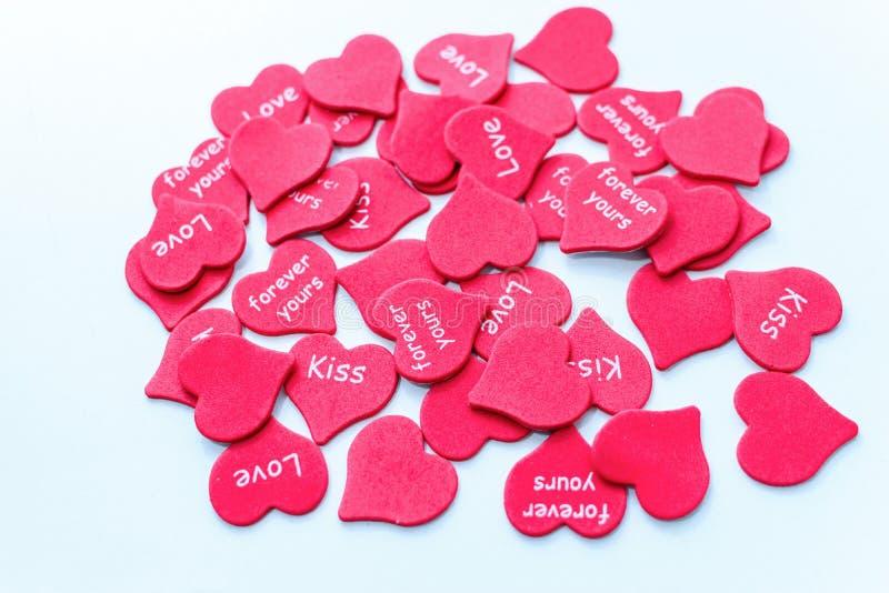 Spridda röda hjärtor som symbol av vitt bröllop för förälskelsebakgrund royaltyfria foton