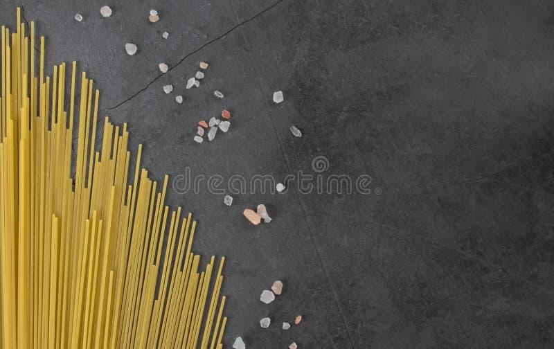 Spridda tunna gula spagetti och kryddor på en grå bakgrund arkivbild