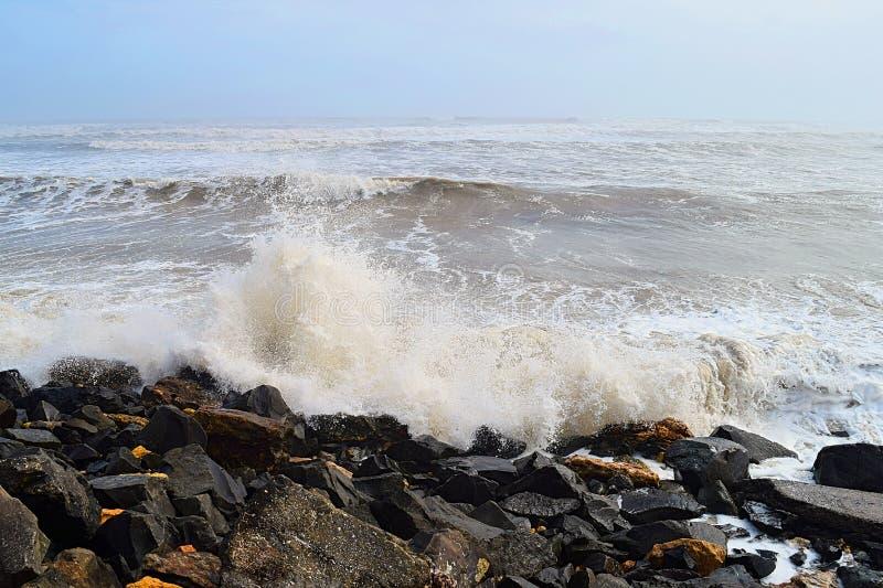 Spridning av vattendroppar med Hitting of Sea Wave to Rocks on Shore - Ocean Natural Aqua Background royaltyfria bilder