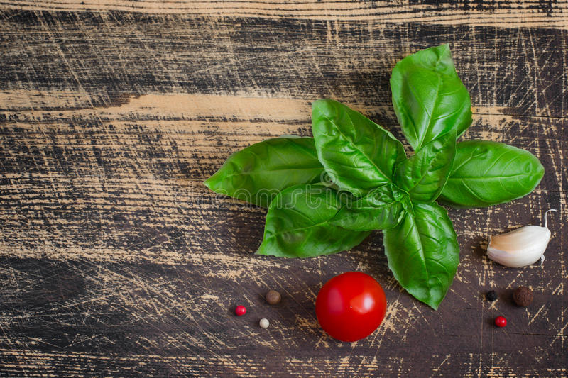 Sprig of basil, cherry tomatoes, spices on the old wooden background stock image