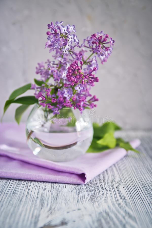 Sprig of lilac still life. Sprig of lilac in a glass round vase on a wooden table still life stock image