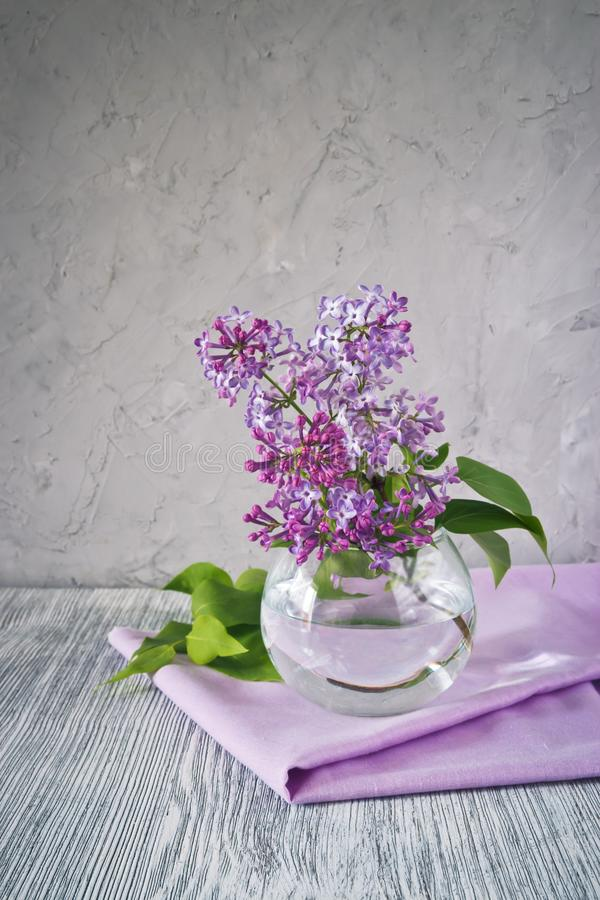 Sprig of lilac still life. Sprig of lilac in a glass round vase on a wooden table still life stock photos
