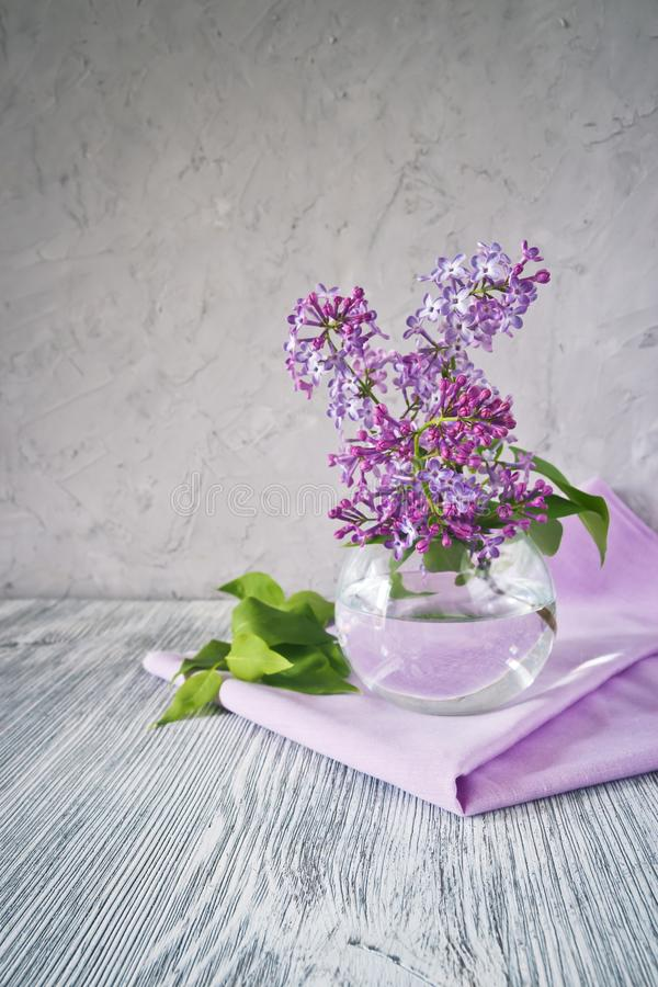 Sprig of lilac still life. Sprig of lilac in a glass round vase on a wooden table still life royalty free stock photography
