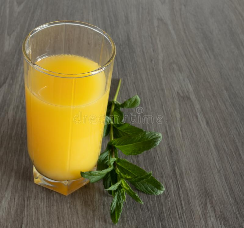 A sprig of mint next to a glass of yellow juice on a wooden table stock images