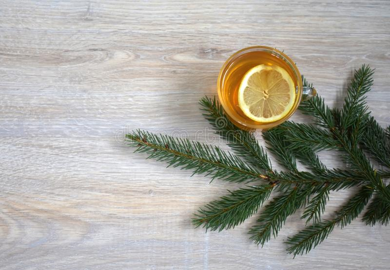 A sprig of spruce with a mug of lemon tea on the background of a. Drink with lemon in a glass Cup decorated with a green twig royalty free stock photo
