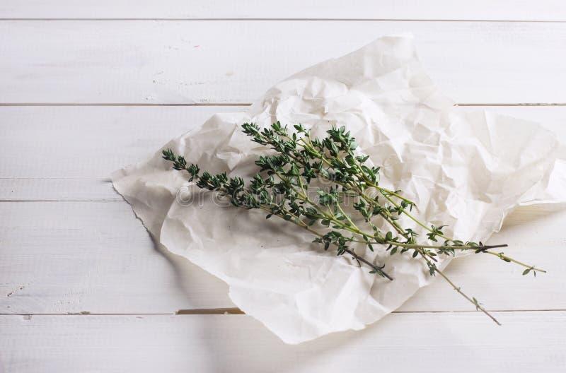 Sprigs тимиана на бумаге на белой деревянной предпосылке стоковое изображение