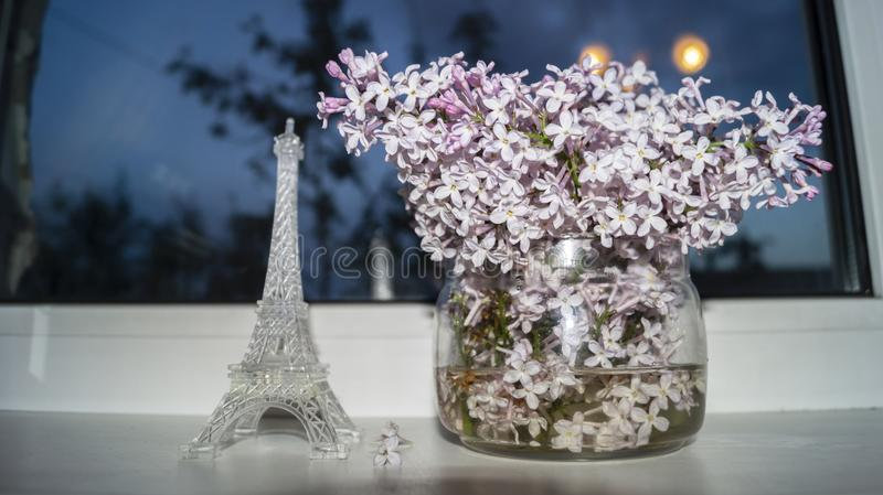 Sprigs of blooming lilac stand on the windowsill. In a glass vase stock photo