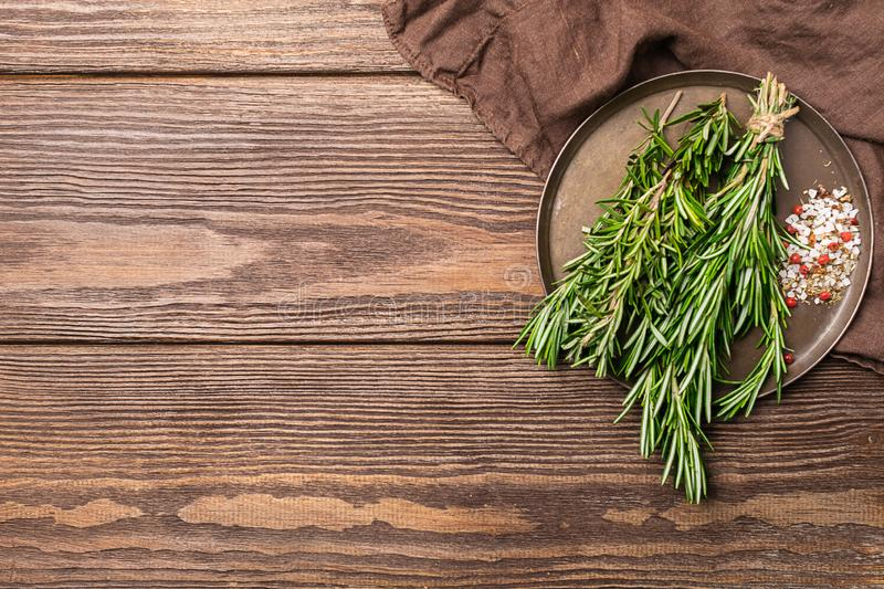 Sprigs of fresh fragrant rosemary in a bunch and other spices on a brown wooden background. Copy space. Flat layout. royalty free stock photo