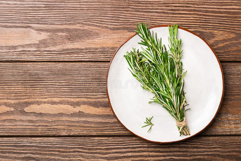 Sprigs of fresh fragrant rosemary are collected in a bun lying on a white plate on a wooden background. Copy space. royalty free stock photo