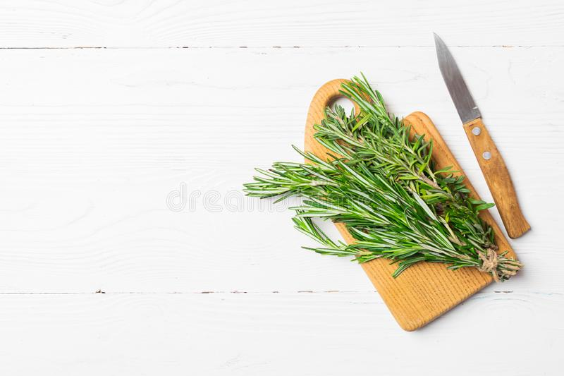 Sprigs of fresh fragrant rosemary on a cutting board on a white wooden background. Copy space. Flat layout. stock images
