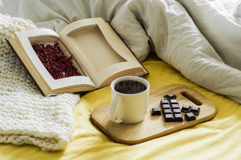 Spring Autumn still life. Breakfast in bed. White bedroom. Sweet home. Books, flowers, chocolate and coffee cup. flat lay stock photo