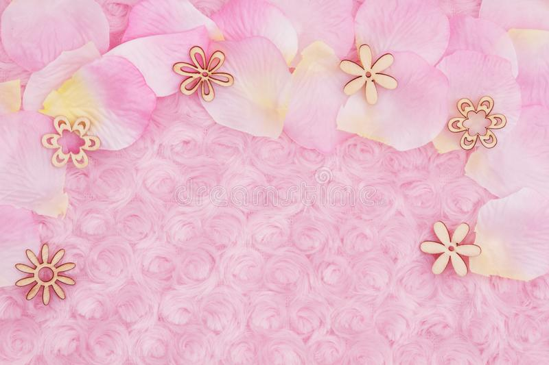 Spring background with a flower petals on pale pink rose plush fabric stock images