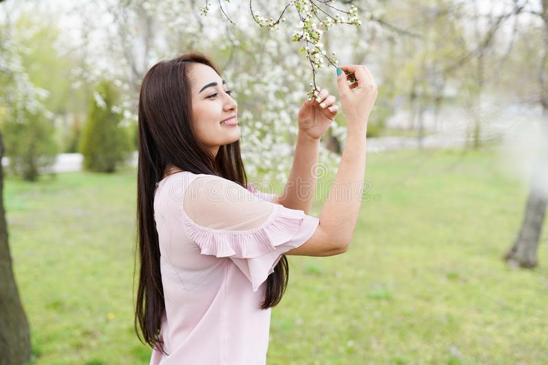 Spring background girl enjoying smell in a flowering garden . copy space . happy young woman royalty free stock image