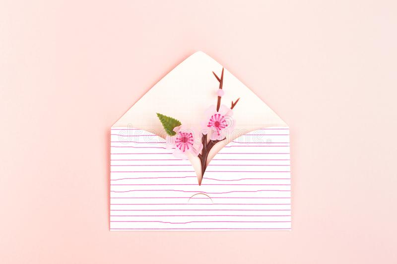 Envelope on pink background. Spring background made with cute envelope with cherry blossom branch. Pastel pink backdrop. Flat-lay, top view. Copy space for your royalty free stock photo