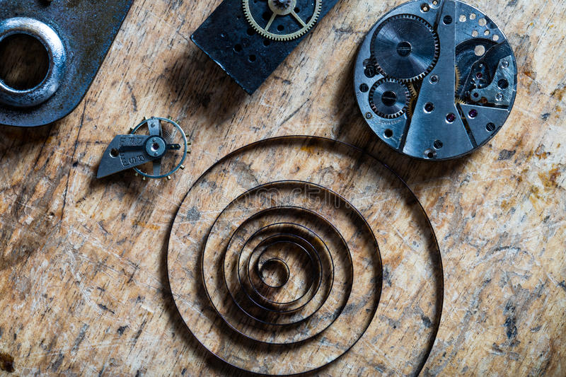 Spring, balance wheel and clockworks on a table. Vertical view (flat layer) of a spring, balance wheel and clockworks on a table of a clockmaker stock image