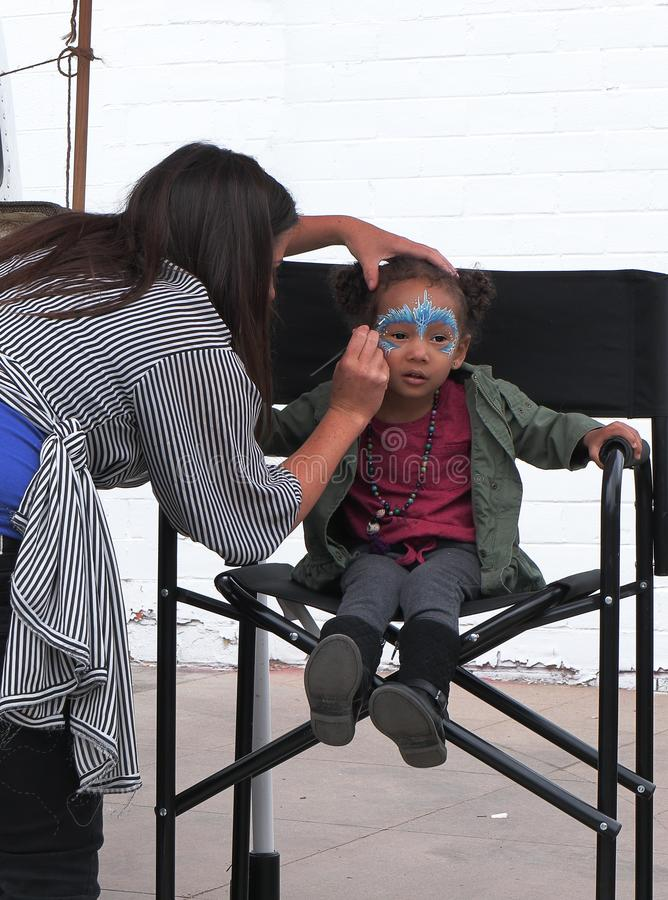 Spring Bazaar in RINO Art District. A girl gets her face painted at the Spring Bazaar in RINO Art royalty free stock photo