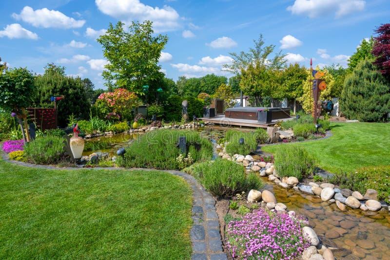 Spring in beautiful garden, pinks, allium, roses flowering on garden creek and pond royalty free stock photos