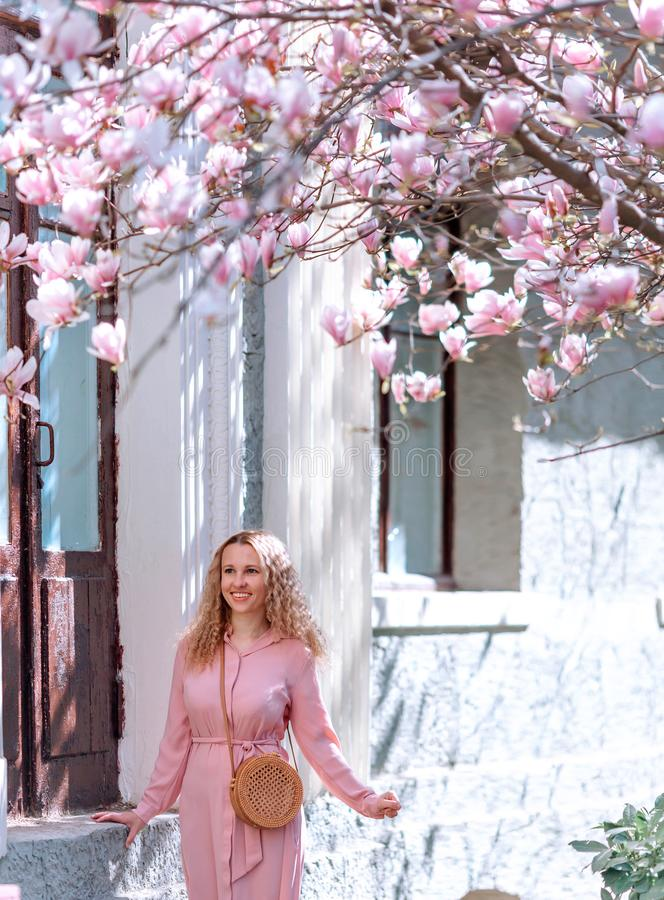 Spring Beautiful romantic girl in fashion dress standing in blooming magnolia trees. Spring concept stock photography