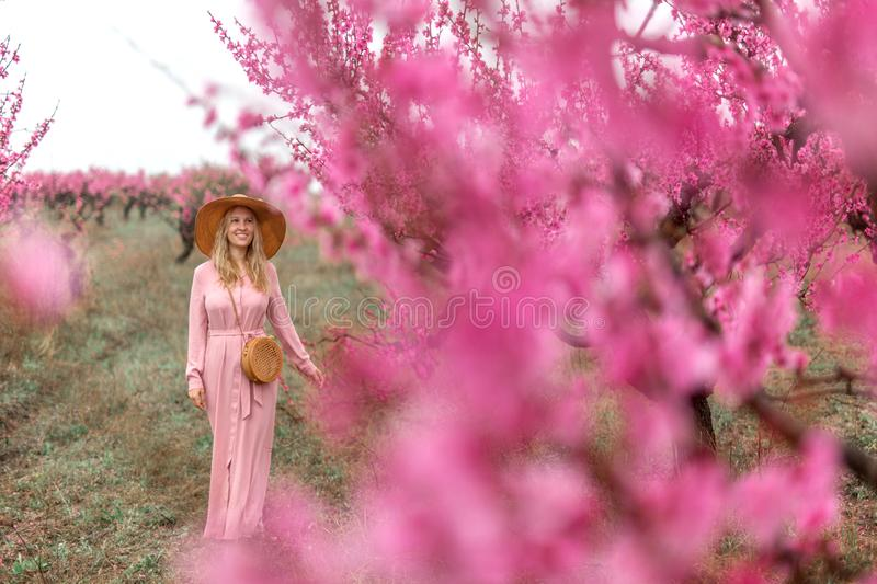 Spring Beautiful romantic girl in fashion dress standing in blooming peach trees. royalty free stock photos