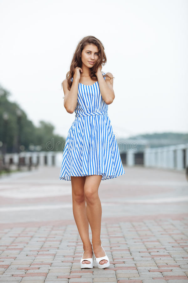 Spring beautiful woman in summer dress walking in city river park enjoying weekend. Playful and beautiful caucasian girl on warm. Spring beautiful lady in summer stock photography