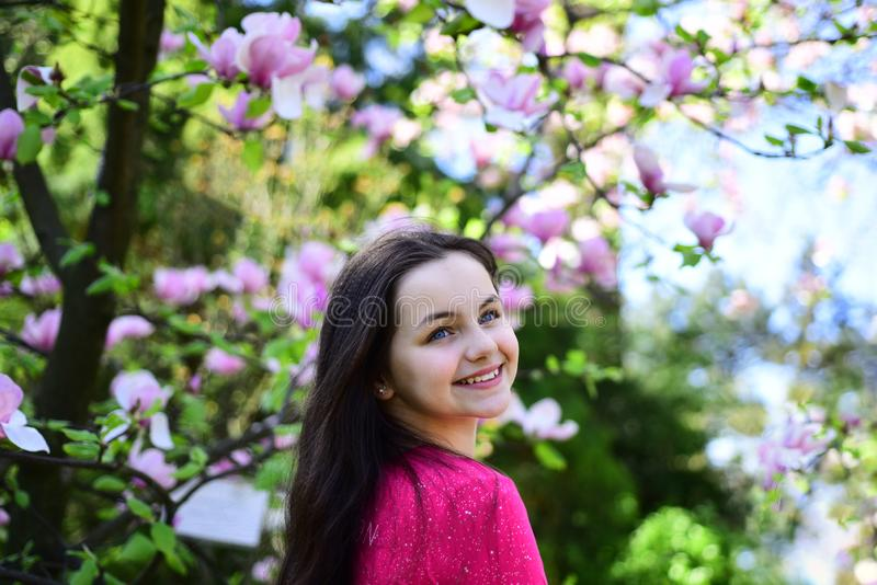 Spring beauty. Cute girl happy smiling on spring landscape. Pretty girl near flowering tree enjoy magnolia blossom royalty free stock image