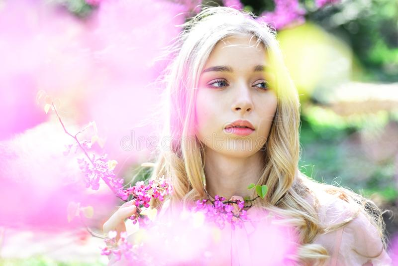 Spring bloom concept. Young woman enjoy flowers in garden, defocused, close up. Girl on dreamy face, tender blonde near. Violet flowers of judas tree, nature stock photography