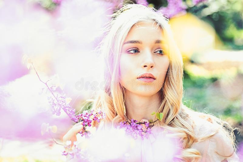 Spring bloom concept. Young woman enjoy flowers in garden, defocused, close up. Girl on dreamy face, tender blonde near. Violet flowers of judas tree, nature stock photo