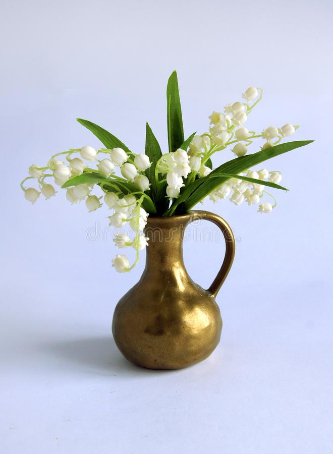 Spring bouquet with lily of the valley. In a bronze vase stock photography